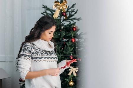 Photo pour Jeune femme en pull chaud tenant branche de baies rouges pour le décor de Noël - image libre de droit