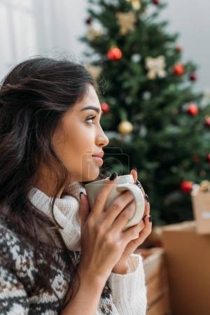 Photo pour Jeune femme réfléchie avec tasse de boisson chaude devant l'arbre de Noël flou - image libre de droit