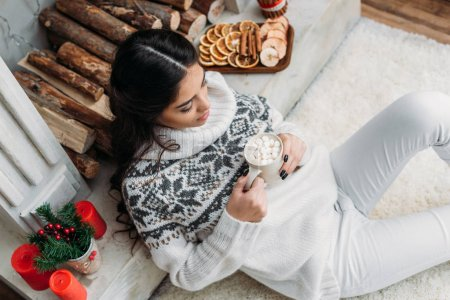 woman with cup of cocoa with marshmallow on christmas