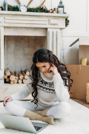 woman in warm sweater working with laptop