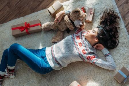Photo pour Vue de dessus de jeune belle femme couchée sur le sol avec ours en peluche et cadeaux de Noël - image libre de droit