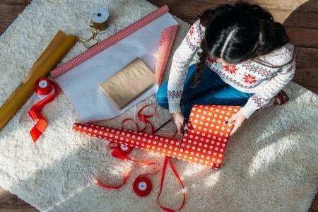 Frau verpackt Weihnachtsgeschenk