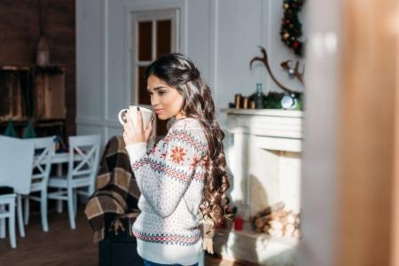 Photo pour Jeune belle femme profiter d'une boisson chaude le matin de Noël - image libre de droit
