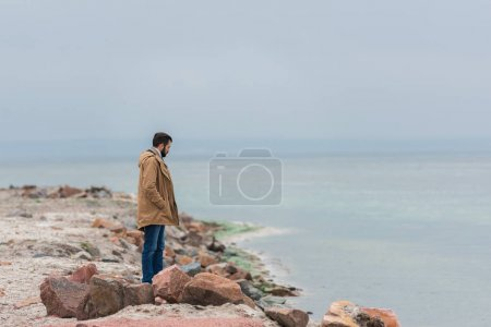 Photo for Lonely sad man standing on rocky seashore - Royalty Free Image