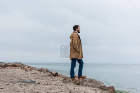 Photo for Lonely handsome man standing on rocky seashore - Royalty Free Image