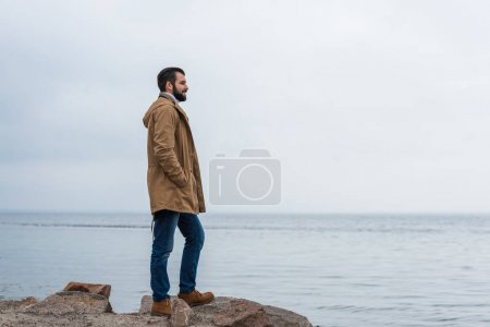 Photo for Lonely man standing on rocky seashore - Royalty Free Image