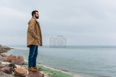 Photo for Thoughtful lonely young man looking at sea - Royalty Free Image