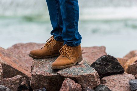 Man in stylish shoes standing on rocks