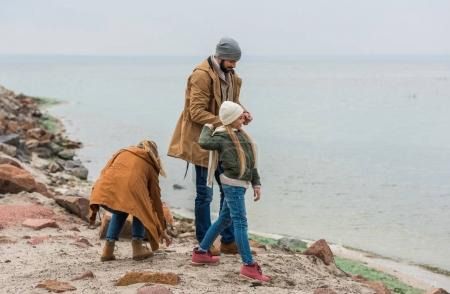 Photo for Young family spending time on beautiful seashore on cold autumn day - Royalty Free Image
