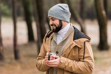 Photo pour Bel homme heureux avec tasse de boisson chaude dans la forêt - image libre de droit