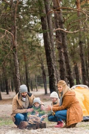 family warming hands with bonfire