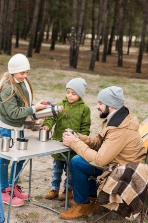father and kids with hot drinks outdoors