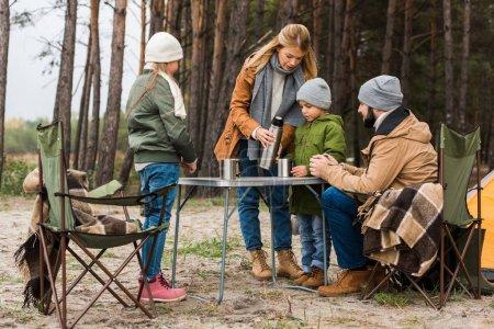 family drinking hot tea outdoors