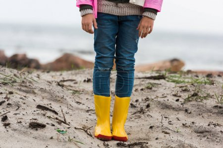 Child in raincoat and rubber boots