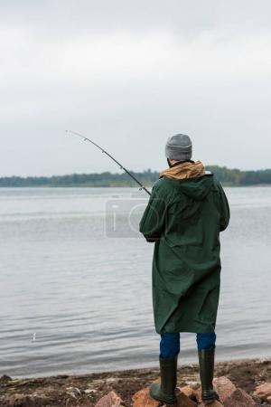 Photo for Lonely man in raincoat and warm clothing fishing on lake - Royalty Free Image