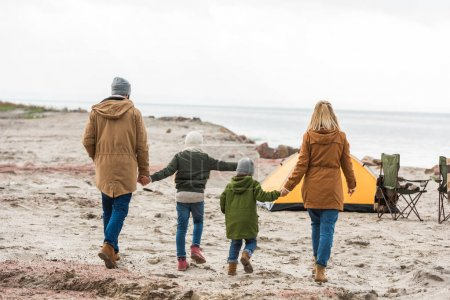 Photo for Back view of family walking to camping tent on seashore - Royalty Free Image