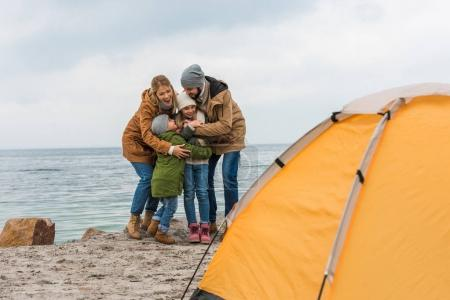 Photo for Happy embracing family having camping on seashore - Royalty Free Image