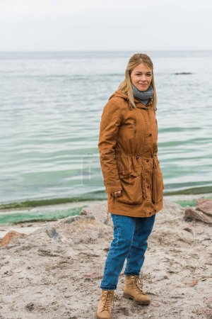 Photo for Lonely woman standing on seahore on cold autumn day - Royalty Free Image