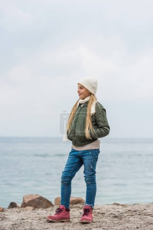 Photo for Little girl standing alone on seashore and looking away - Royalty Free Image