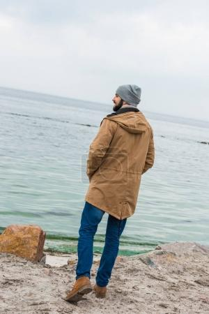 Photo for Handsome lonely man looking at sea on cloudy autumn day - Royalty Free Image
