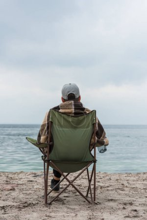 Photo for Lonely man sitting on chair at seashore on cloudy autumn day - Royalty Free Image
