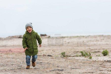 Photo pour Adorable petit garçon courir par plage de sable fin sur froid jour d'automne - image libre de droit