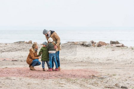 family emracing on seashore