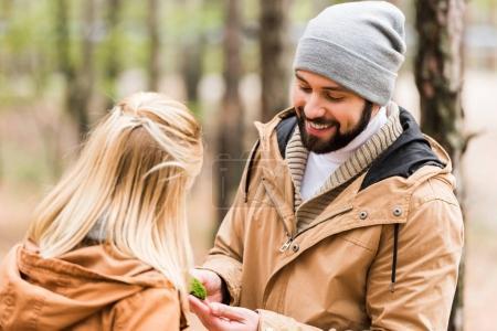 Photo pour Heureux beau homme montrant mousse de forêt à petite amie - image libre de droit