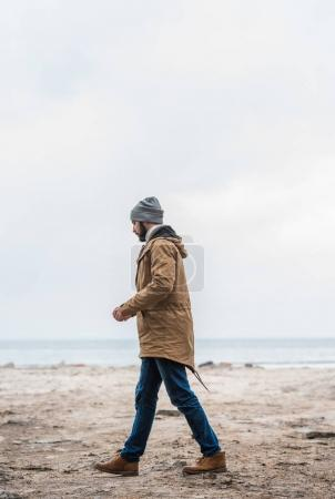 Photo for Side view of handsome lonely man walking by seashore - Royalty Free Image