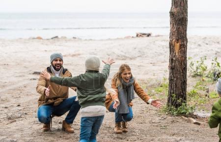 kids running to parents on seashore