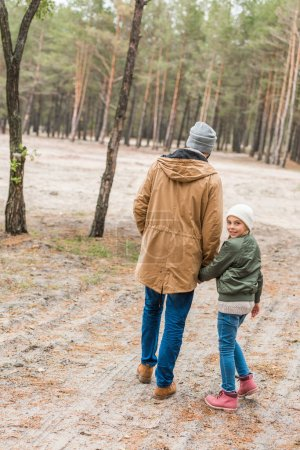 father and daughter walking by forest