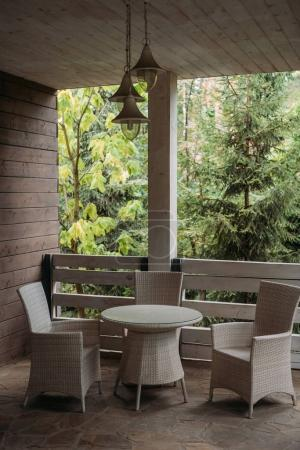 Photo for Wicker chairs and round table on terrace in country house - Royalty Free Image