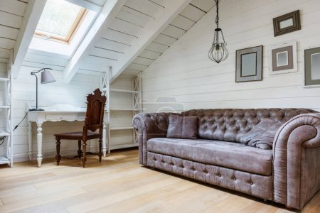 Photo for Classic sofa, empty frames on wall and table with chair in cozy room - Royalty Free Image