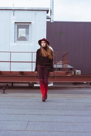 Woman in stylish outfit walking on roof