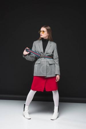 woman in gray jacket and red skirt