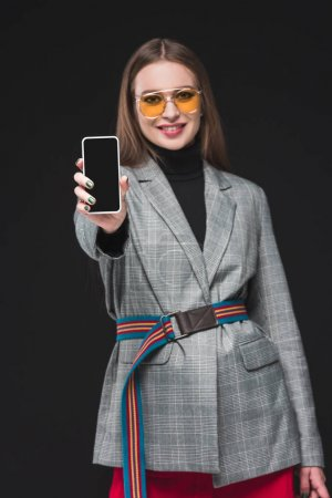 woman in autumn outfit showing smartphone