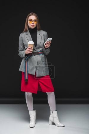 Photo pour Belle femme en automne permanent tenue avec le smartphone et le café dans la tasse de papier - image libre de droit