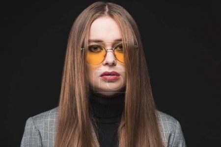Photo pour Portrait de femme élégante en lunettes de soleil jaunes et veste grise isolée sur noir - image libre de droit