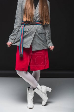 Photo for Cropped image of Beautiful woman standing in gray jacket and red skirt - Royalty Free Image