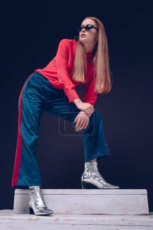 Photo pour Superbe femme en tenue chic et lunettes noires, debout sur des escaliers en bois sur un fond noir - image libre de droit