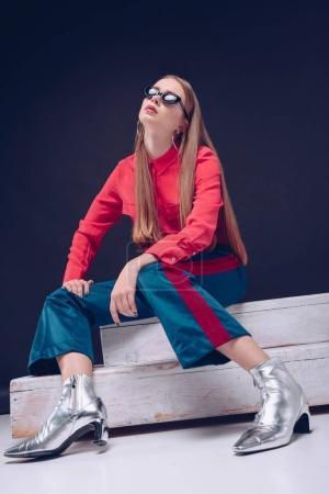 Photo pour Jolie fille en chemise rouge et lunettes de soleil noires assises sur un escalier en bois - image libre de droit