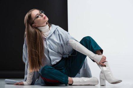 femme en tenue élégante assise sur le sol