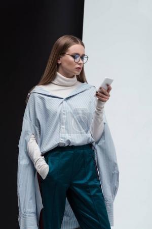 Foto de Chica elegante suéter, camisa y gafas mirando smartphone en la mano - Imagen libre de derechos