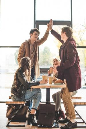 Foto de Dos amigos masculinos dando alta cinco en café - Imagen libre de derechos