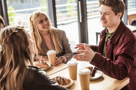 Photo for Young men and women sitting at cafe and spending time together - Royalty Free Image