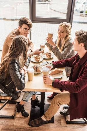 Photo pour Quatre amis assis au café avec café et croissants - image libre de droit