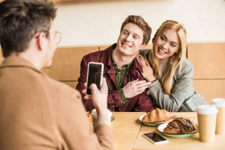 Photo for Man taking photo of friends with smartphone in a cafe - Royalty Free Image