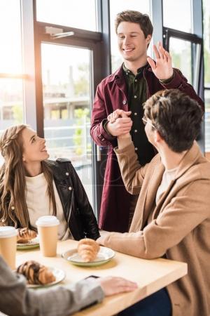 Photo pour Homme de serrer la main à un ami et en agitant la main aux filles - image libre de droit