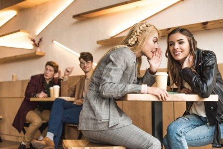 Foto de Chicas cotilleando sobre hombres jóvenes sentados en una mesa adyacente en un café - Imagen libre de derechos