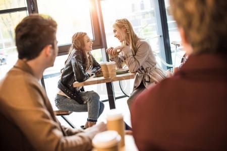 men looking at girls at adjacent table
